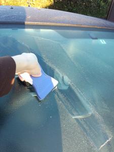 フロントガラスの氷を削り取る